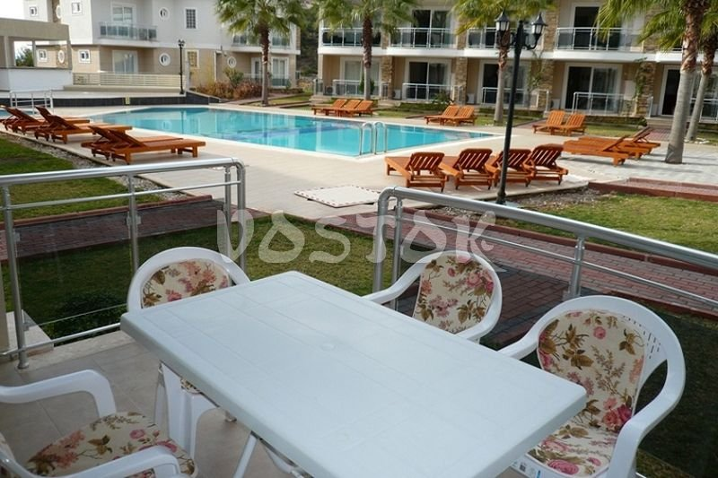 Terrace is equipped with table and chairs and overlooks to swimming pool - Blue Green Apartments in Calis Fethiye
